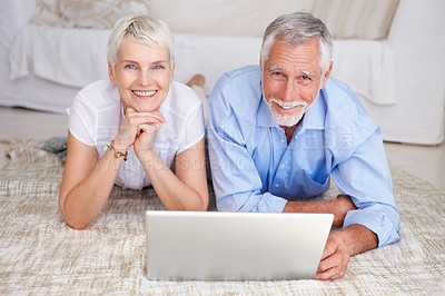 Buy stock photo A senior retired couple lying down with a laptop