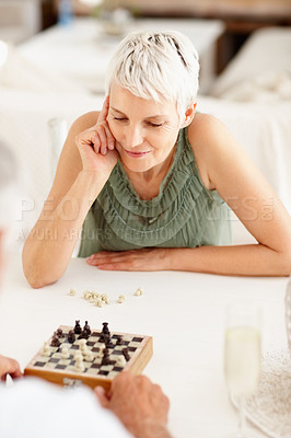 Buy stock photo Charming mature woman playing a game of chess