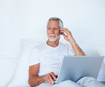 Buy stock photo Portrait of a senior old cheerful man speaking on a mobile while working on laptop