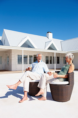 Buy stock photo Happy senior couple enjoying themselves outdoors with their holiday house in the background