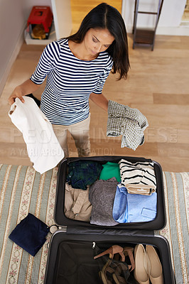 Buy stock photo Shot of a woman packing her suitcase