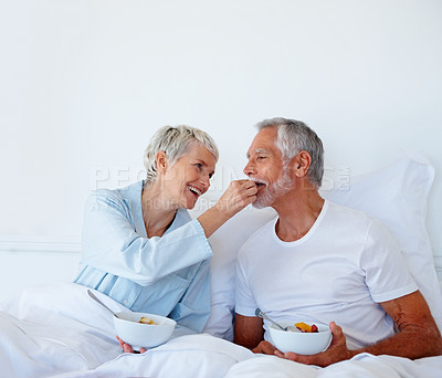 Buy stock photo Charming elderly woman feeding her husband fruits, in bed