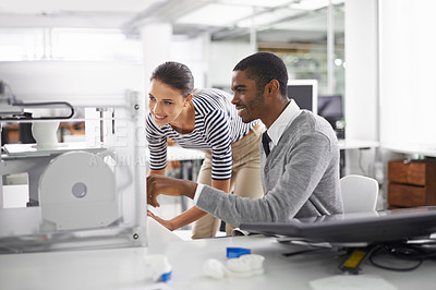 Buy stock photo A shot of two colleagues looking at a 3D printer