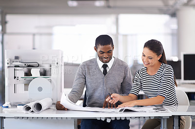 Buy stock photo A shot of two colleagues working happily together in the office