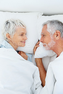 Buy stock photo Profile view of a happy couple having a good time in bed