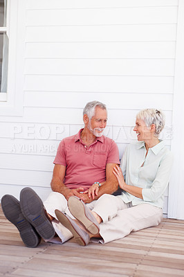 Buy stock photo Charming couple sitting together on the floor of their house