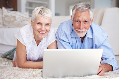 Buy stock photo Portrait of a senior couple lying on the floor, using a laptop