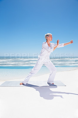 Buy stock photo Full length image of a mature old woman practicing martial arts at the sea shore