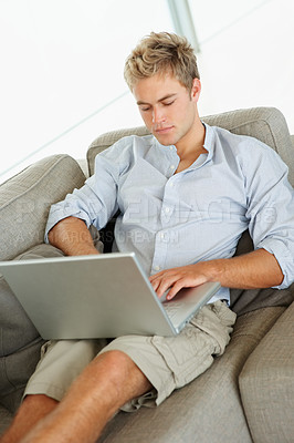 Buy stock photo A handsome confident young man working on a laptop