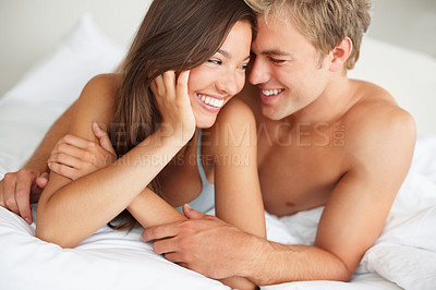 Buy stock photo Cute young couple laughing and snuggling playfully on their bed