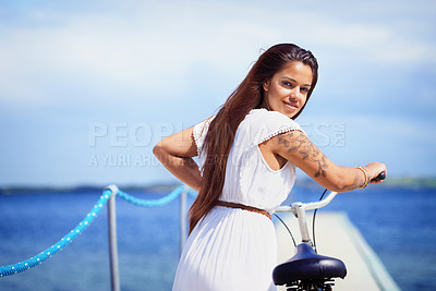 Buy stock photo Cropped shot of a gorgeous tattooed young woman pushing her bicycle along a pier