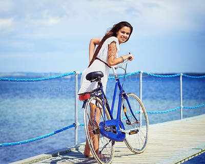 Buy stock photo Full length shot of a gorgeous tattooed young woman pushing her bicycle along a pier
