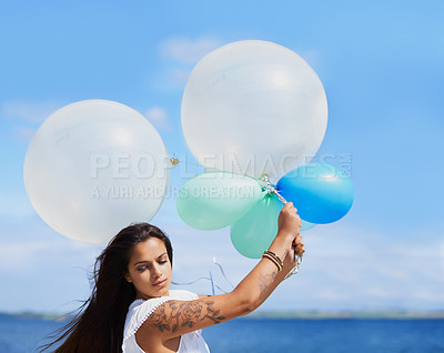 Buy stock photo Cropped shot of a gorgeous tattooed young woman holding balloons