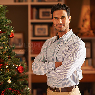 Buy stock photo Cropped shot of a man standing next to a christmas tree with folded arms