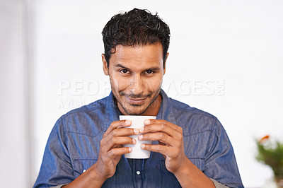 Buy stock photo A handsome man smiling while holding a cup of coffee