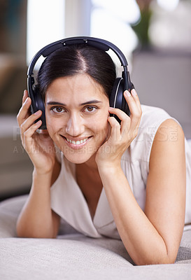 Buy stock photo Portrait of an attractive young woman listening to music while relaxing at home