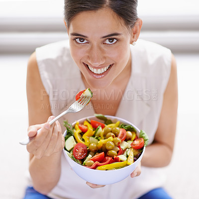 Buy stock photo High angle portrait of an attractive young woman eating a bowl of salad