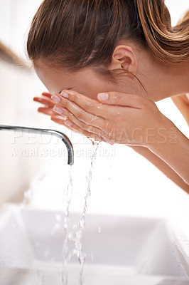 Buy stock photo Closeup shot of a young woman washing her face over a sink