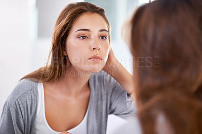 Buy stock photo Over the shoulder shot of an attractive young woman looking at her reflection in a mirror