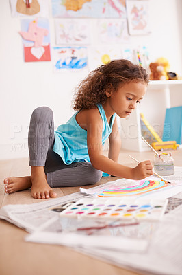 Buy stock photo Shot of a little girl lying on the floor and painting a picture