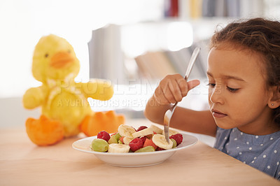 Buy stock photo Shot of a cute little girl eating fruit salad with her plush toy on the table