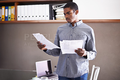 Buy stock photo Shot of a handsome young businessman looking over some paperwork in his home office