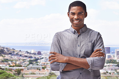 Buy stock photo Portrait of a handsome young man standing against a city backdrop