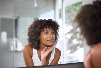 Buy stock photo Shot of an attractive young woman looking at herself in the bathroom mirror