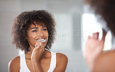 Buy stock photo Shot of a a young woman brushing her teeth