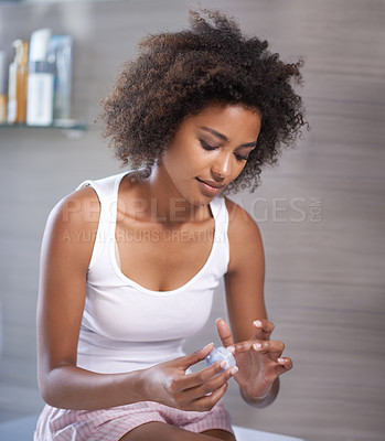 Buy stock photo Shot of an attractive young woman applying cream to her skin
