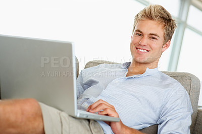 Buy stock photo An attractive confident young man working on a laptop