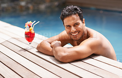 Buy stock photo Shot of a handsome young man sitting in a pool with a cocktail