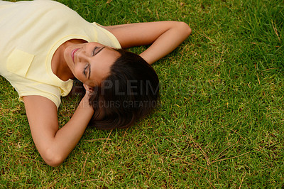 Buy stock photo High angle shot of a young woman lying on the grass