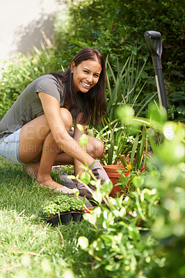 Buy stock photo Full length shot of a pretty brunette woman bending down and working in her garden