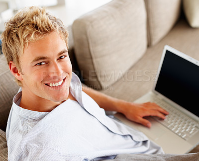 Buy stock photo Portrait of a happy young man at home working on a laptop