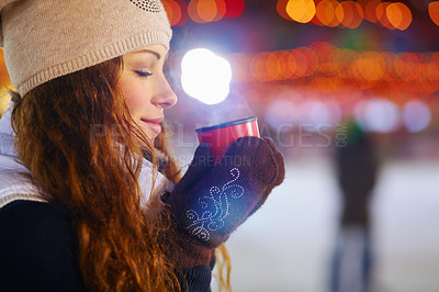 Buy stock photo A young woman looking content as she stands outside enjoying a warm beverage