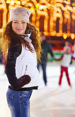 Buy stock photo Portrait of a beautiful young woman standing on an ice rink at night
