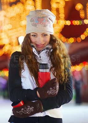 Buy stock photo Portrait of a young woman standing in an ice rink holding a flask