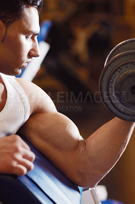 Buy stock photo Cropped shot of a handsome young man lifting weights