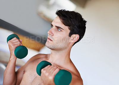 Buy stock photo A cropped shot of a focused young man lifting dumbbells at home