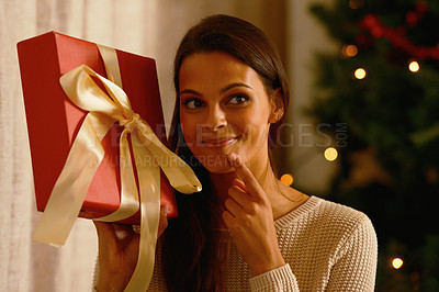 Buy stock photo Portrait of an attractive female pretending she doesn't know what is inside the present