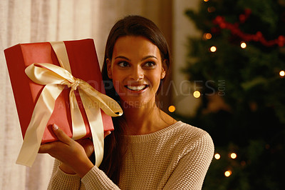 Buy stock photo Shot of a young woman happily holding onto a Christmas gift