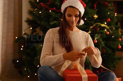 Buy stock photo Smiling young woman wrapping a Christmas gift indoors