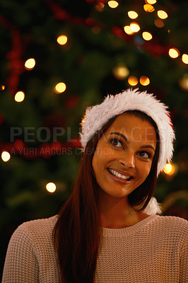 Buy stock photo An attractive ethnic female thinking in front of a christmas tree