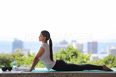 Buy stock photo Shot of a beautiful young woman doing yoga by a window overlooking the city