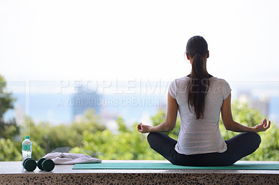 Buy stock photo A young woman meditating on a yoga mat by a window overlooking the city