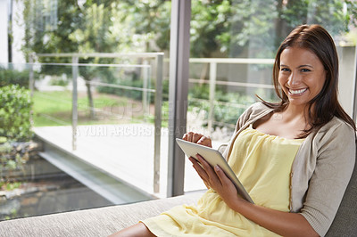 Buy stock photo Shot of an attractive young woman using a digital tablet while relaxing indoors
