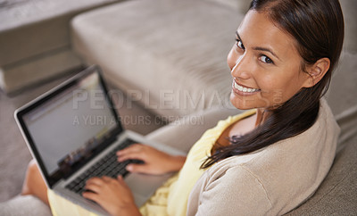 Buy stock photo Portrait of an attractive young woman using her laptop while sitting on the sofa