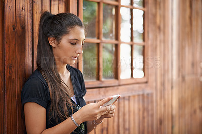 Buy stock photo A pretty teenage girl using a mobile phone while standing outside a cottage