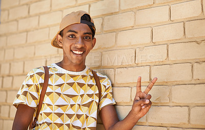 Buy stock photo Shot of a teenage boy showing the peace sign while standing against a wall